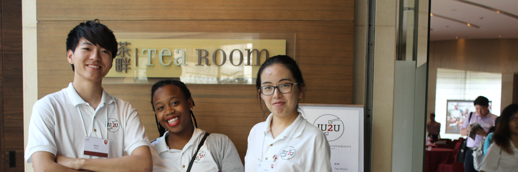 Three IU students stand and smile in front of a sign that reads The Tea Room