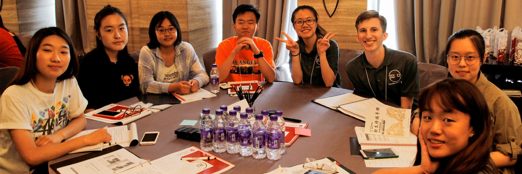 A group of IU2U orientation students from Beijing sit together at a table along with two IU2U orientation leaders
